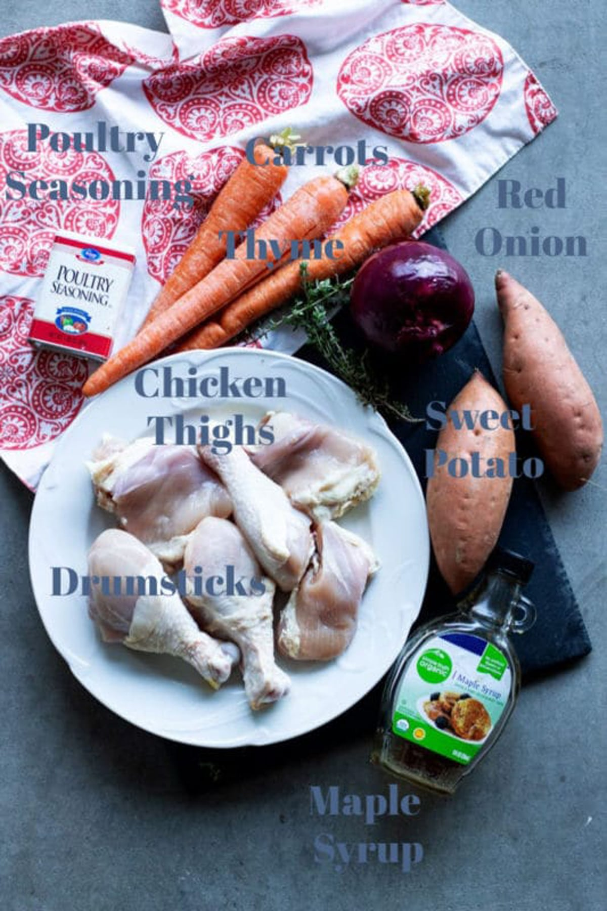 Chicken thighs and drumsticks, carrots, red onion, sweet potato, thyme, maple syrup, seasoning on table.