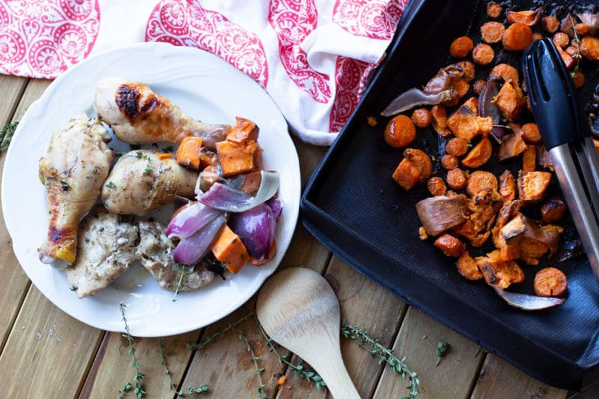 White plate with oven baked chicken, side of carrots, sweet potatoes, and red onions.