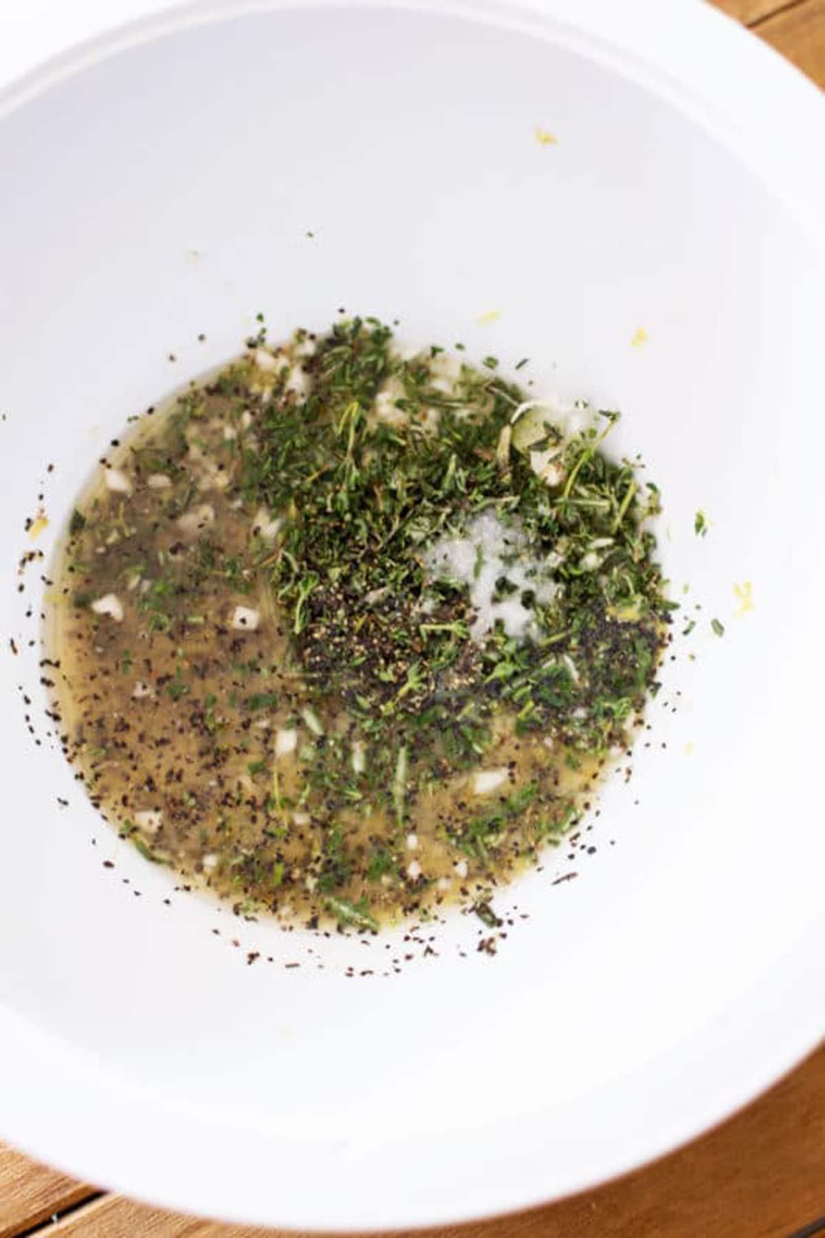 White bowl containing lemon juice, rosemary, thyme, salt and pepper for a Lemon Garlic Thyme Chicken recipe.