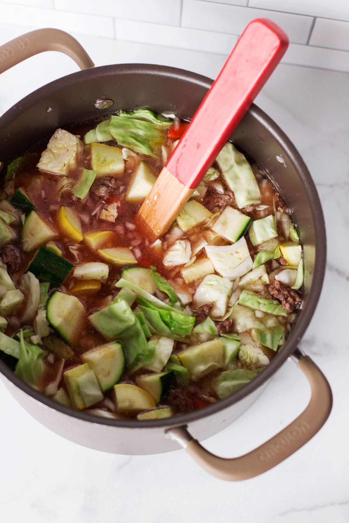 Pot containing a soup with cabbage, squash, zucchini, and hamburger meat.