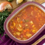 Purple pyrex dish containing tomato based Poor Man's Stew which includes squash, hamburger meat, corn and zucchini, chives and bread on purple napkin.