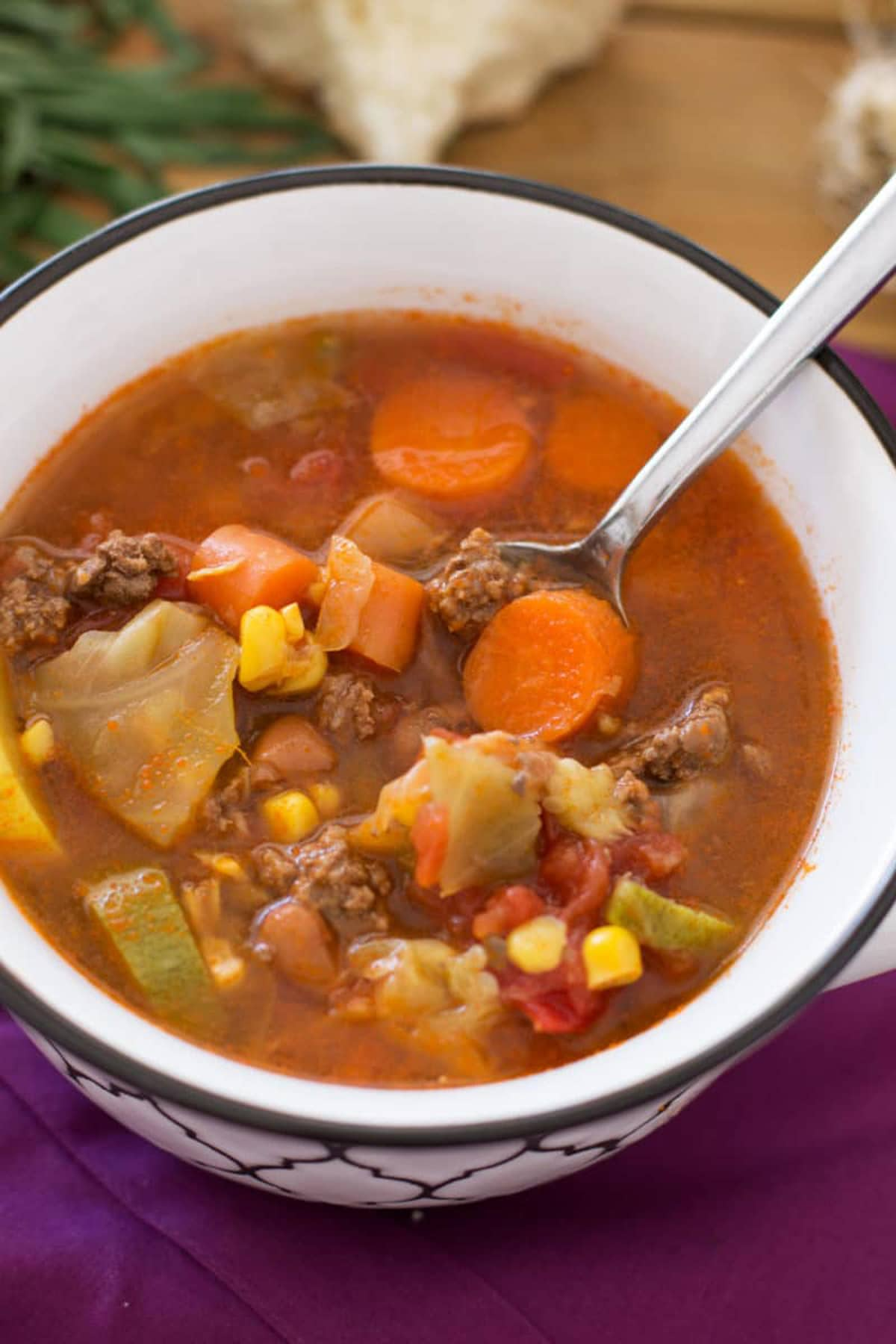Spoonful of Poor Man's Soup in a white bowl containing cabbage, carrots, corn and tomatoes.