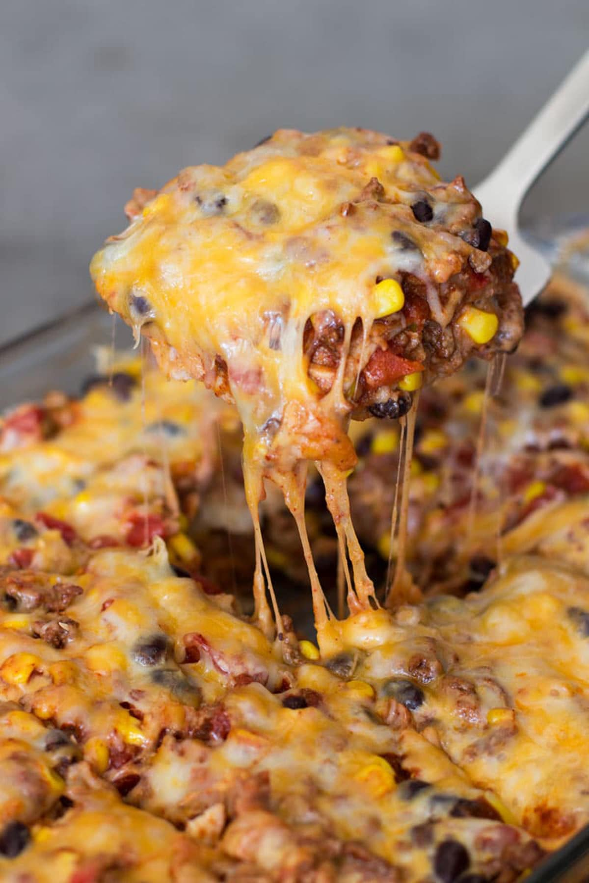 Spatula containing a piece of mexican casserole topped with melted cheese.