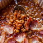 Aluminum pan containing smoker baked beans, spoon in pan.