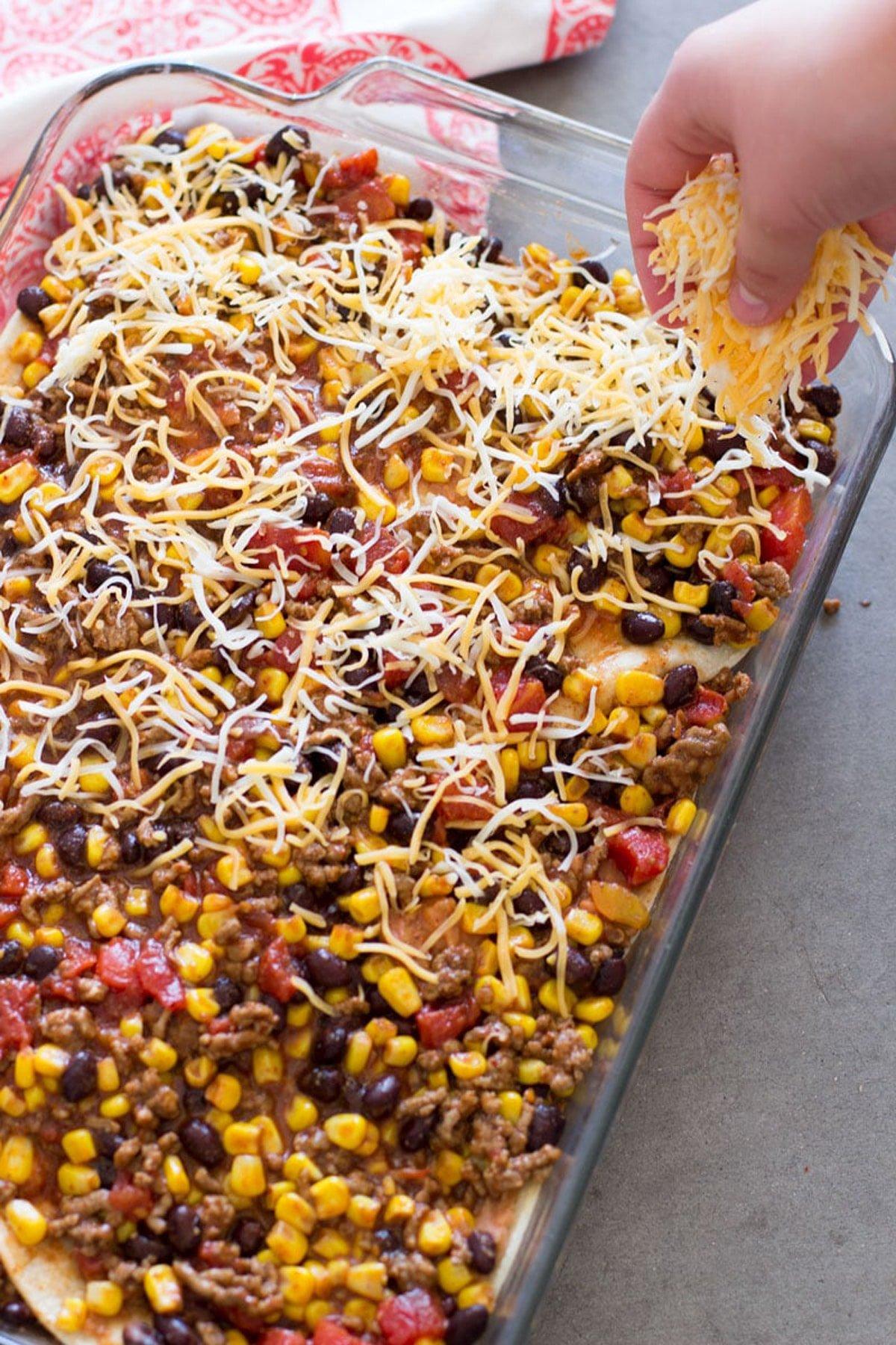 Person adding shredded cheese to enchilada casserole.