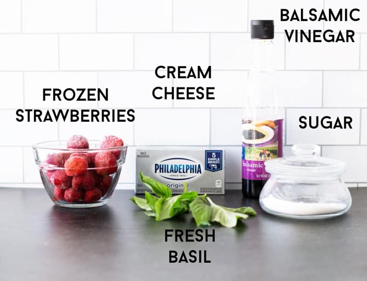 Bowl of frozen strawberries, cream cheese, fresh basil, balsamic vinegar, and sugar on a counter.