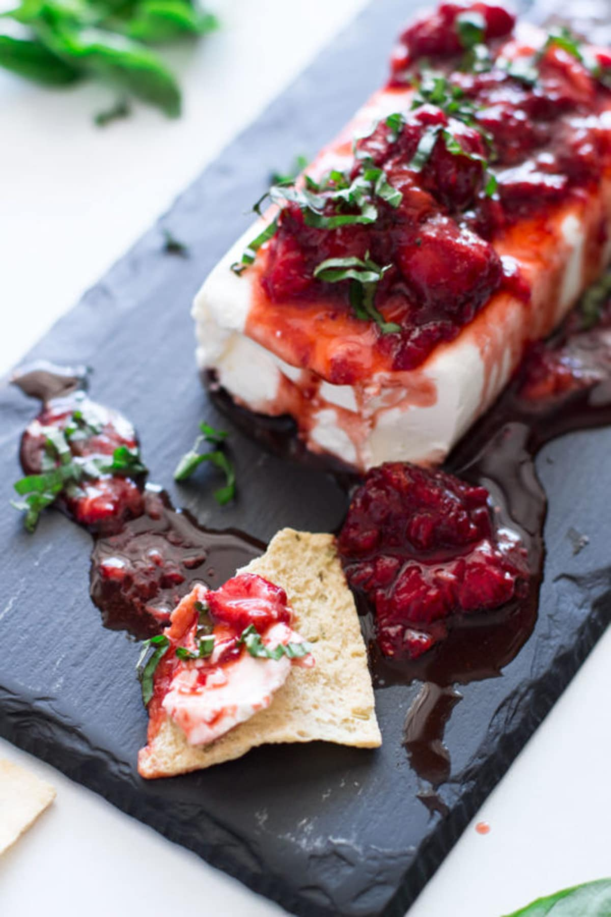 Cream cheese dip served on a pita chip topped with strawberry basil sauce.