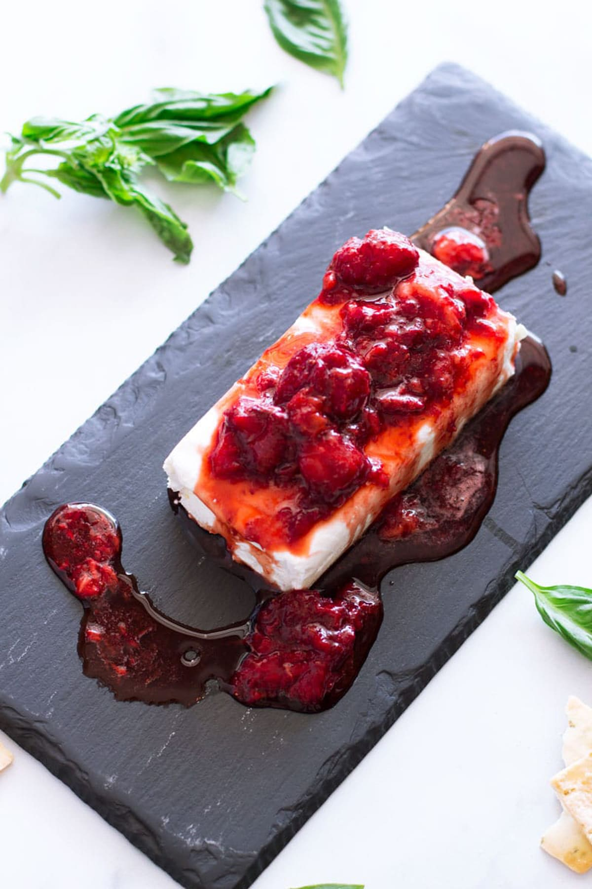Strawberry sauce on cream cheese, basil on table.