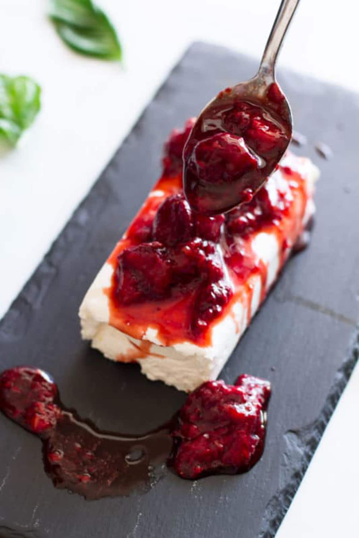 Spoonful of strawberry sauce on a block of cream cheese, basil on table.