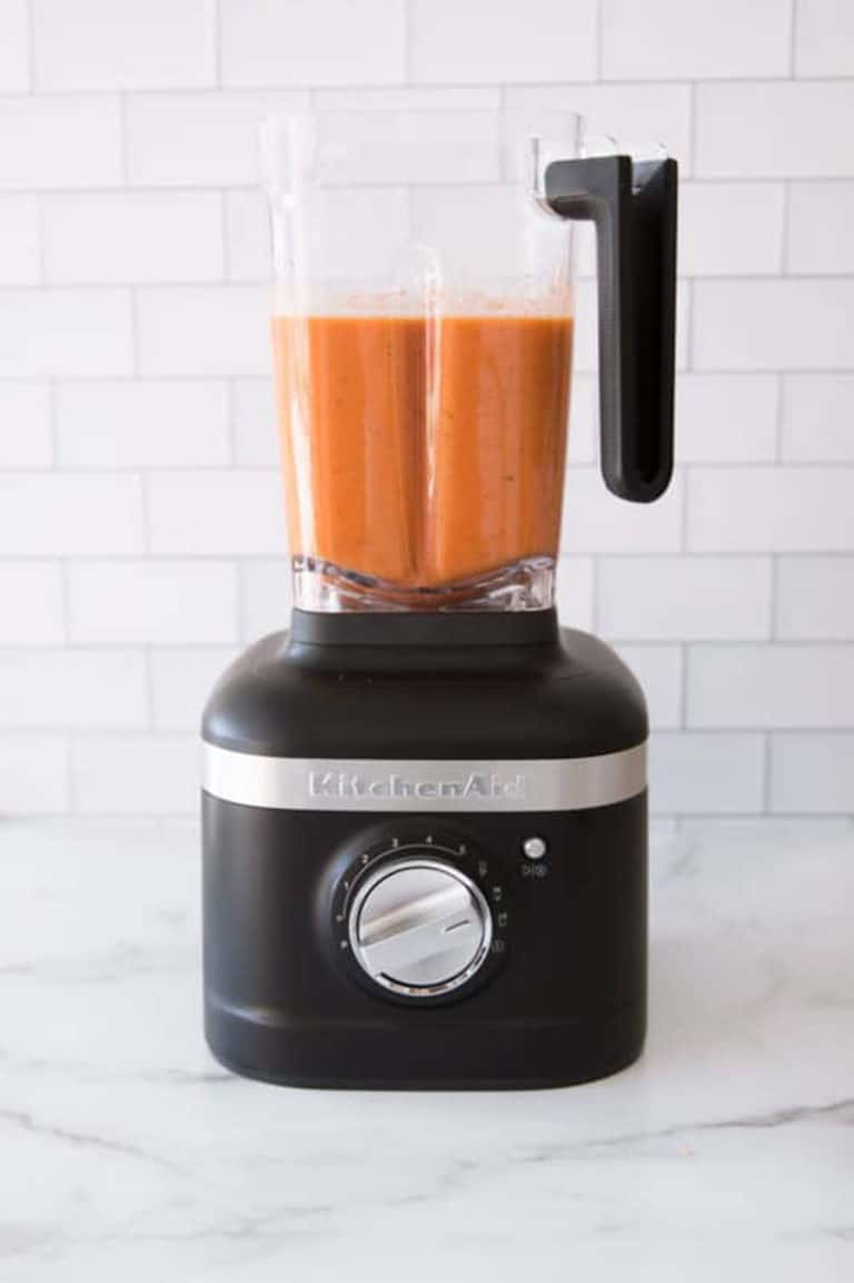 KitchenAid blender containing pureed tomato soup.