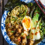 A bowl containing zoodles. bok choy, egg, and chopsticks on side of bowl.