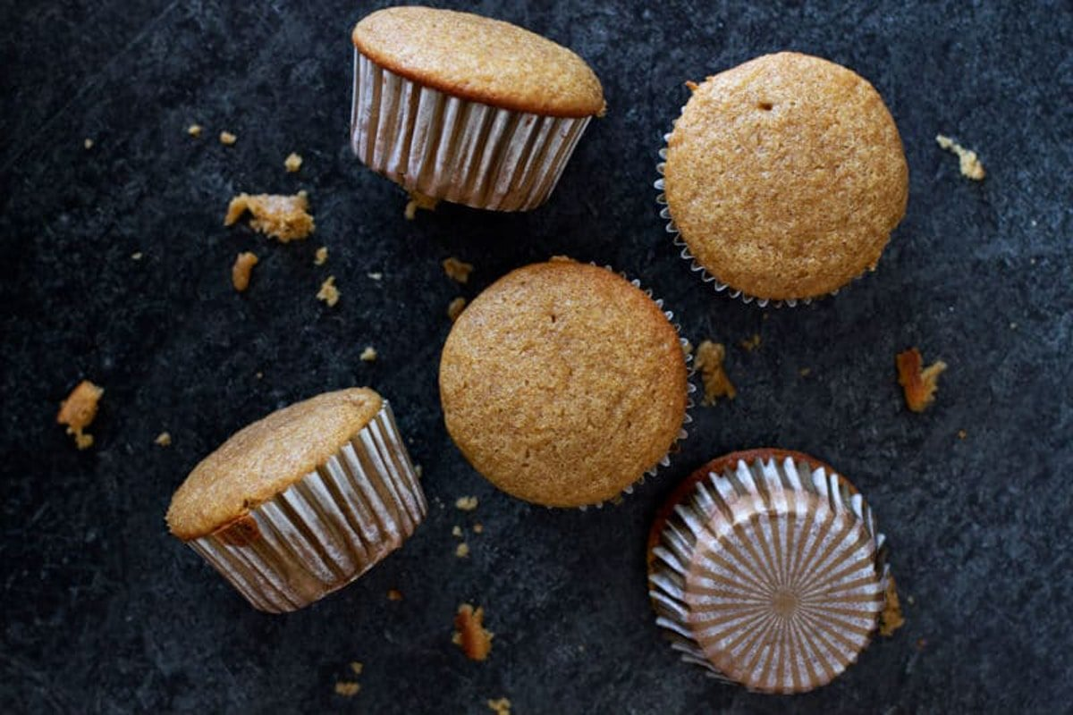 5 acorn squash muffins sitting on a black granite counter, bread crumbles on counter.