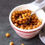 Red striped bowl containing chili lime chickpeas, spoon in bowl.