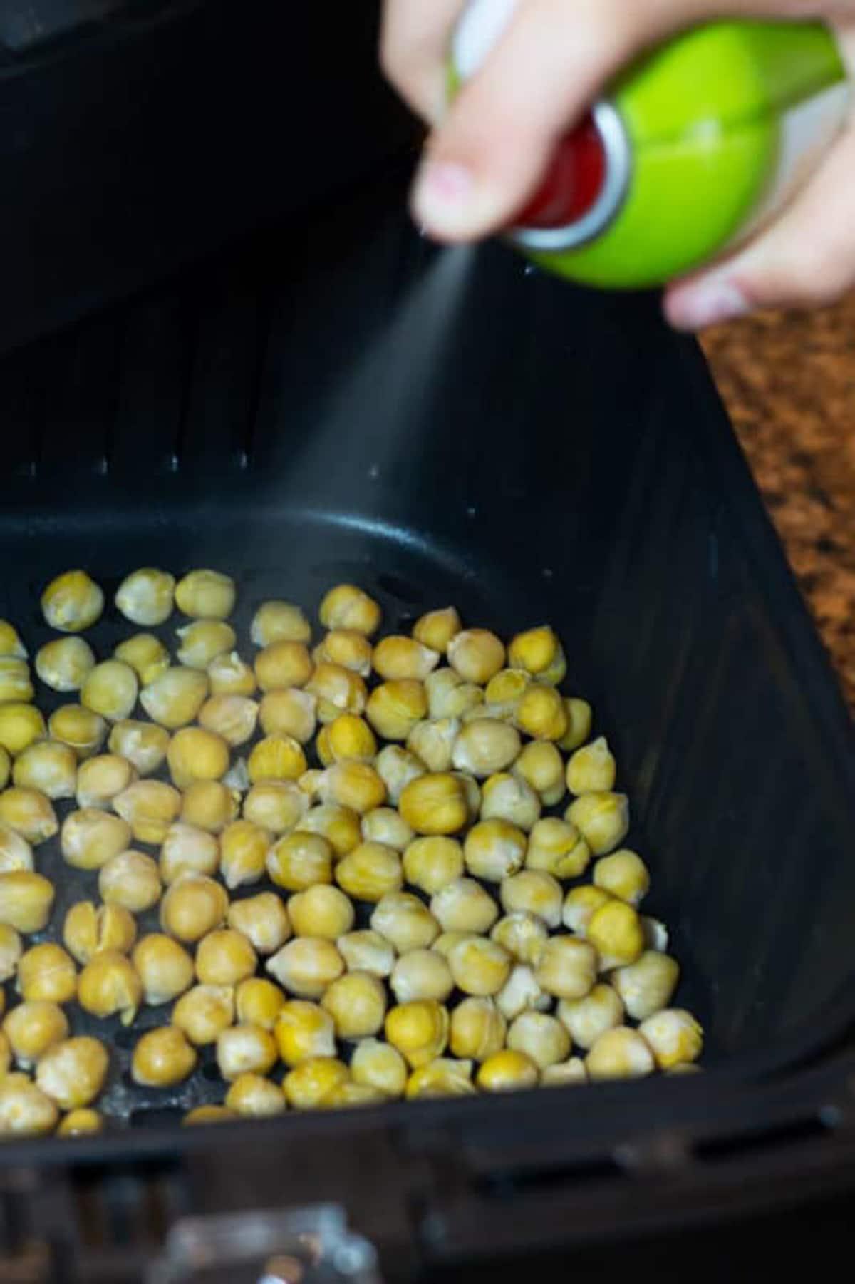 Non-stick spray on chickpeas in an air fryer basket.