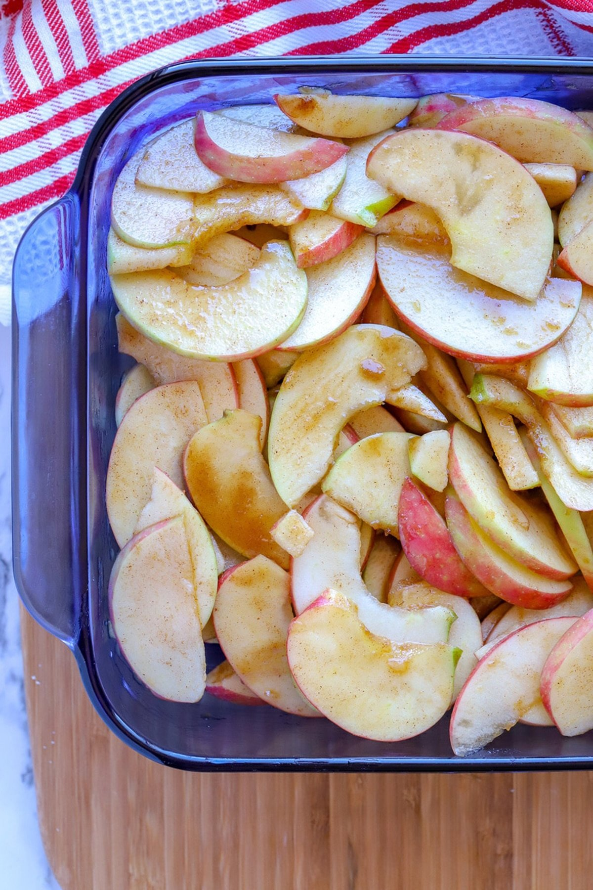 Blue Pyrex dish containing cinnamon apples, red and white napkin on table.