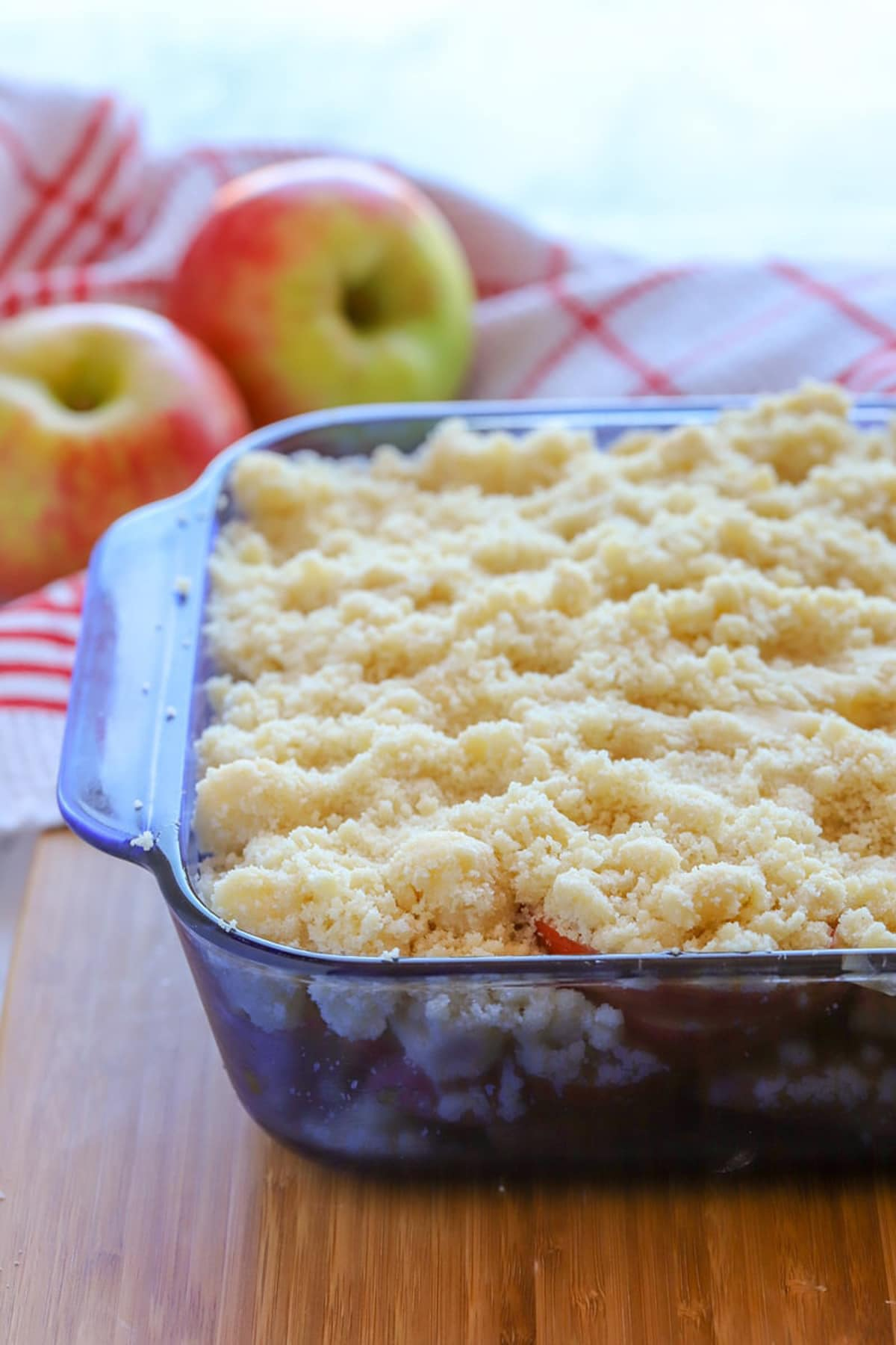 Blue pyrex dish containing an Apple Crumble before baking, 2 red apples on table.