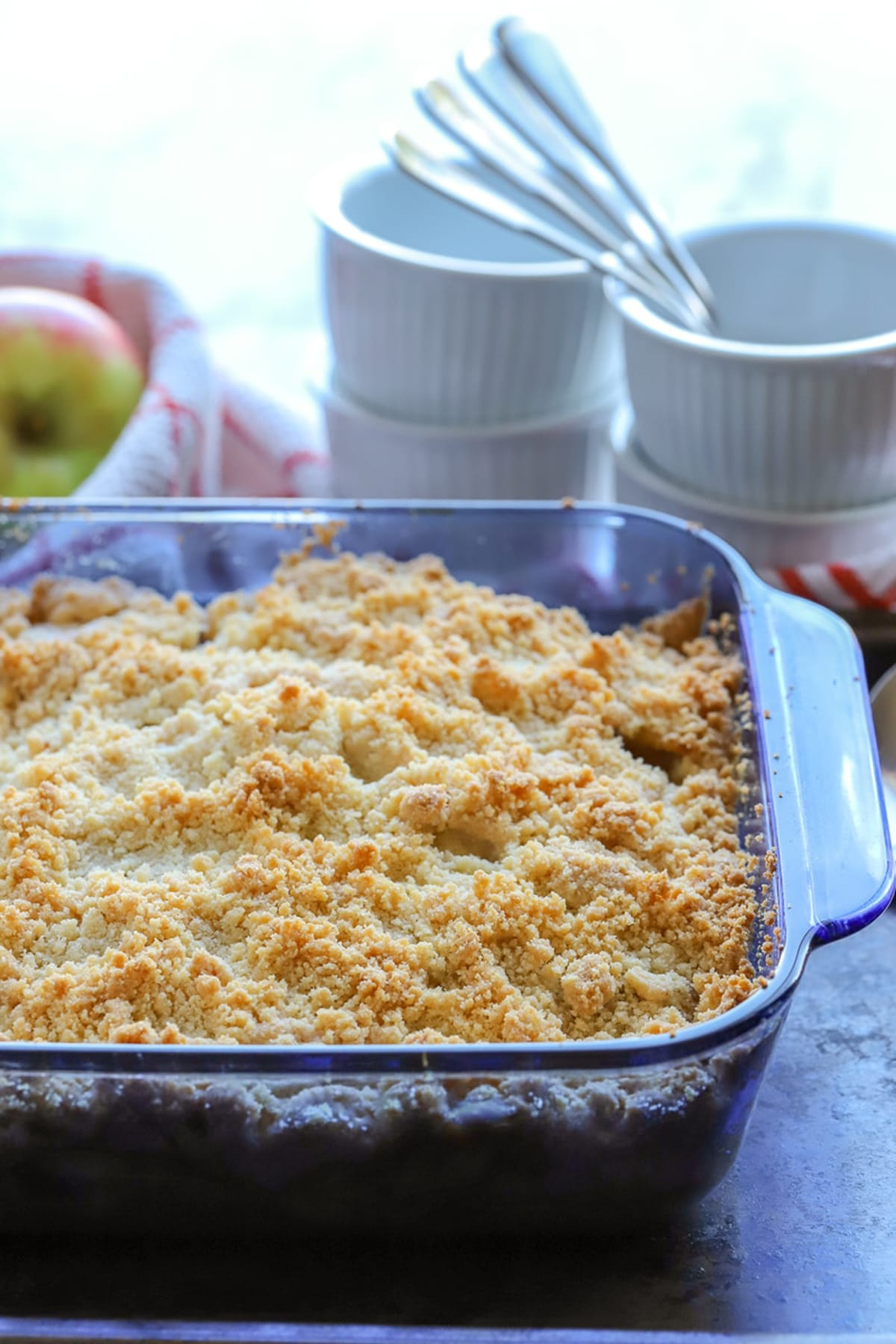 Pyrex dish containing a cooked Gluten Free Apple Crumble Fresh from the Oven, bowls and spoons on table.