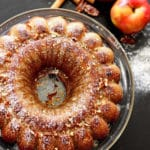 Apple pumpkin bundt cake sitting on a glass cake platter, 2 red apples with cinnamon stick and pecans on a black table.