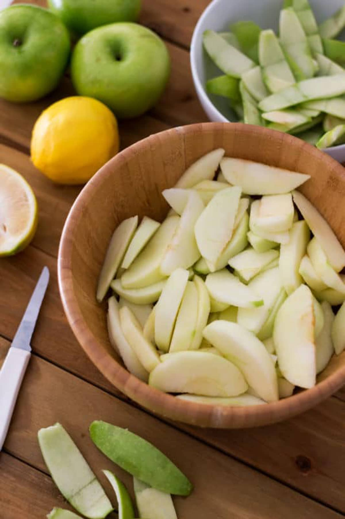 Wooden bowl containing sliced Granny Smith apples sitting on a wood table.