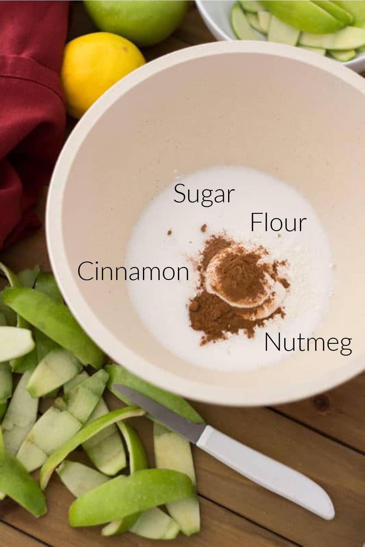 Wooden bowl containing flour, cinnamon, nutmeg and flour, granny smith apple peelings on table.