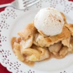 Piece of apple pie served on a white lace place sitting on a red table, topped with Vanilla ice cream and cinnamon.