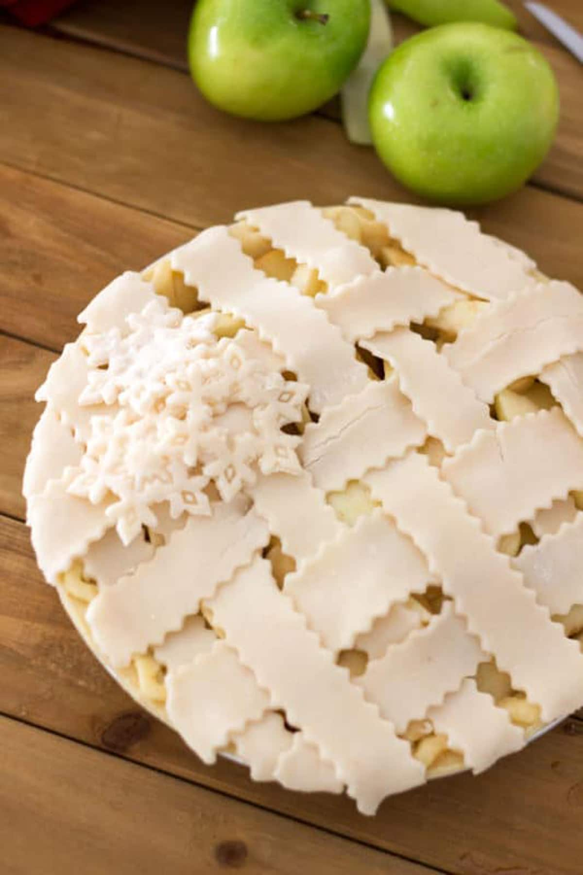 Homemade pie covered with lattice pie crust, 2 granny smith apples on table.