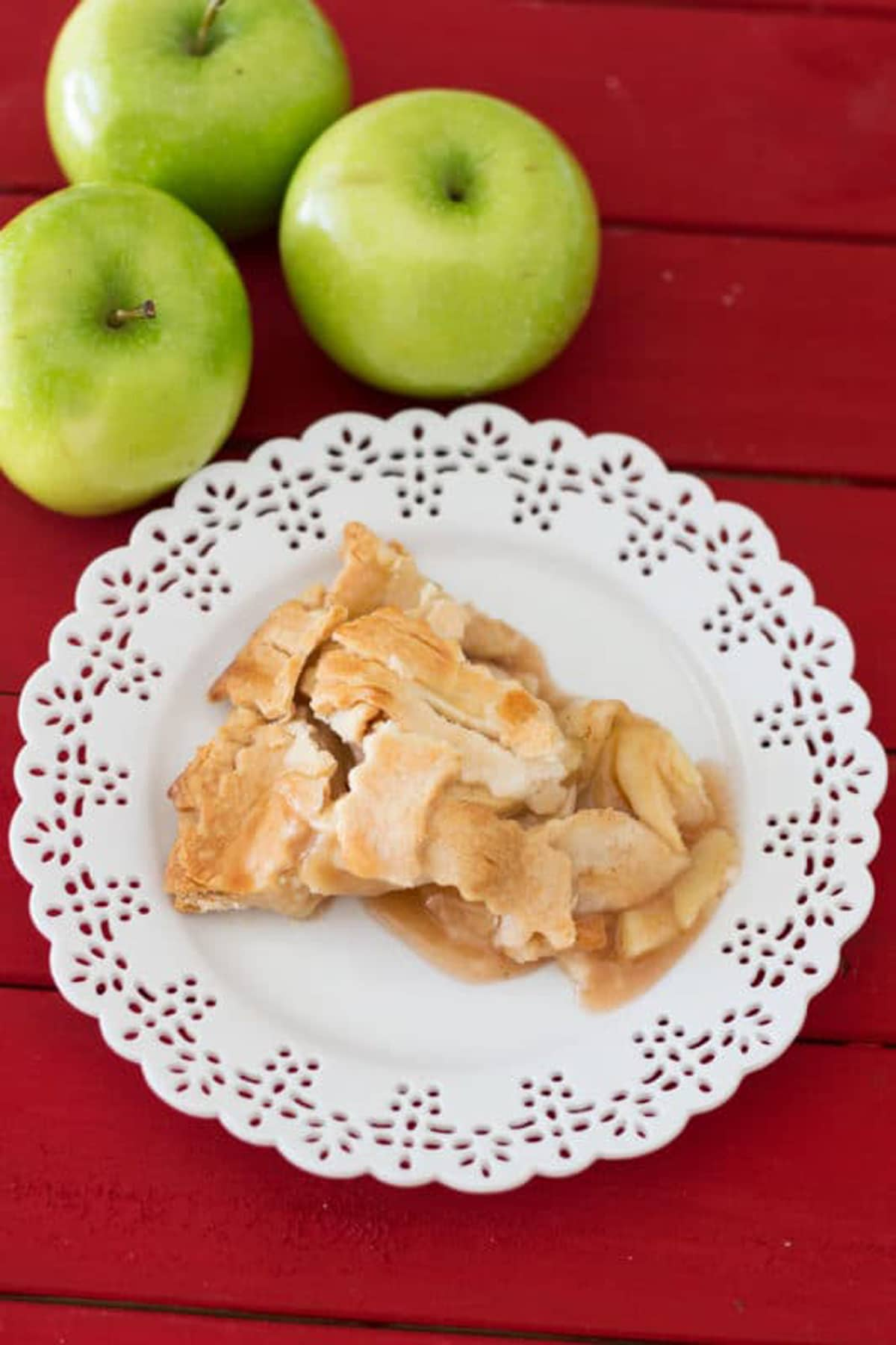 White lace place containing a piece of homemade apple pie sitting on a red table, 3 granny smith apples on table.