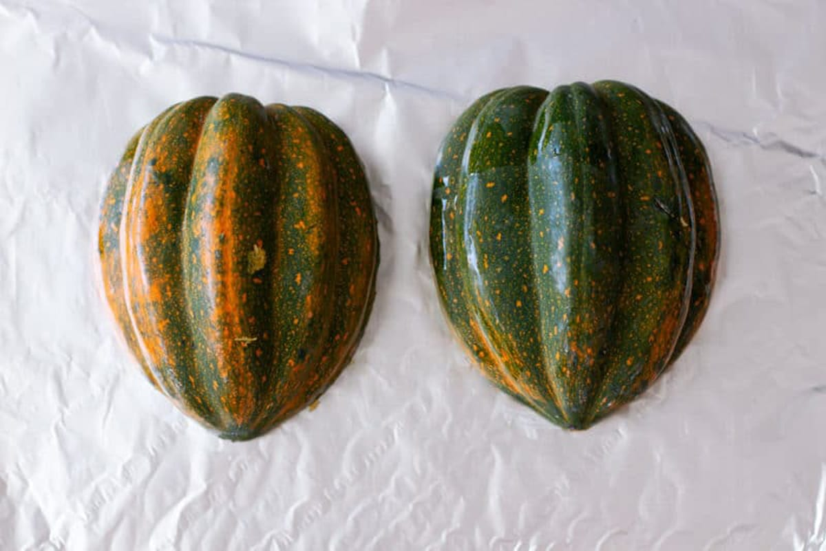 Acorn squash cut in half turned shell side up on a cookie sheet lined with aluminum foil.