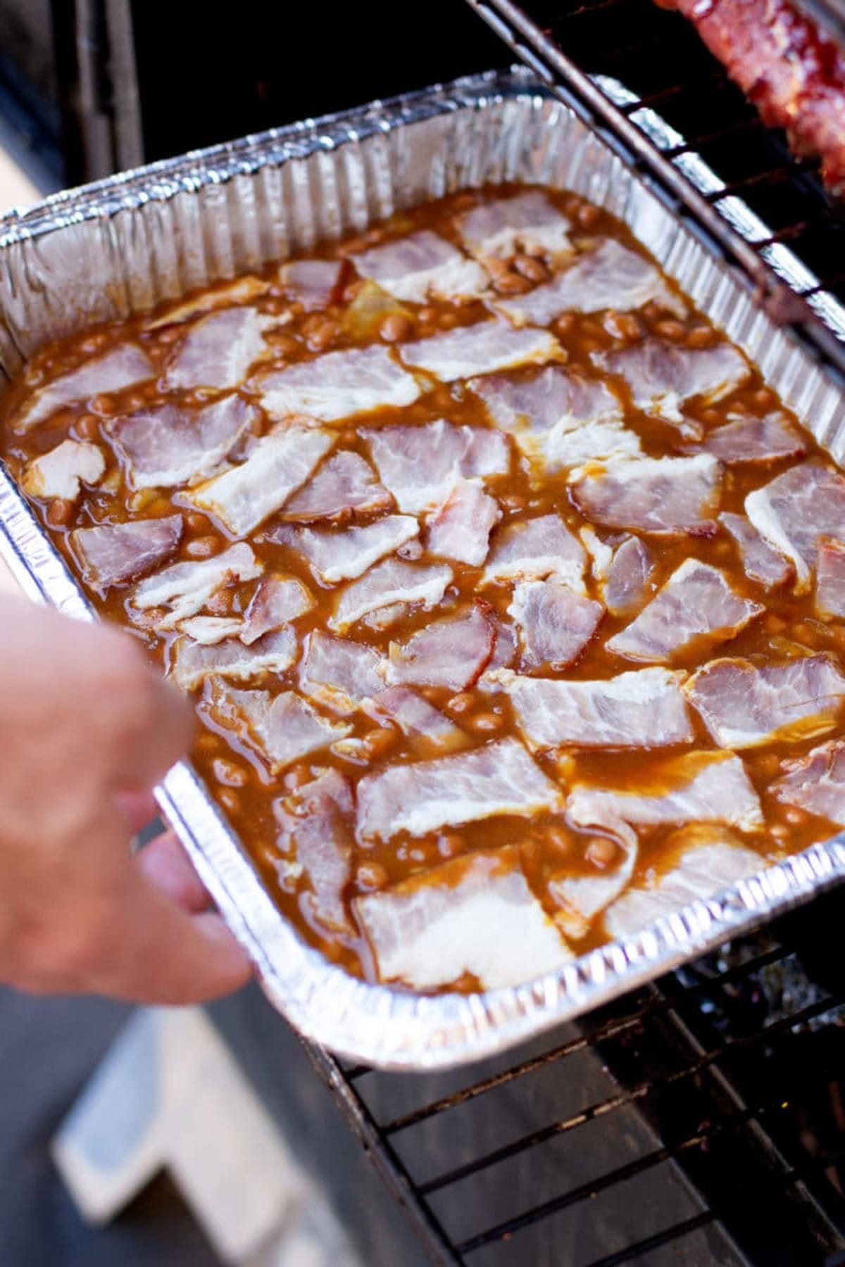 Baked beans in an aluminum pan being placed in a smoker.