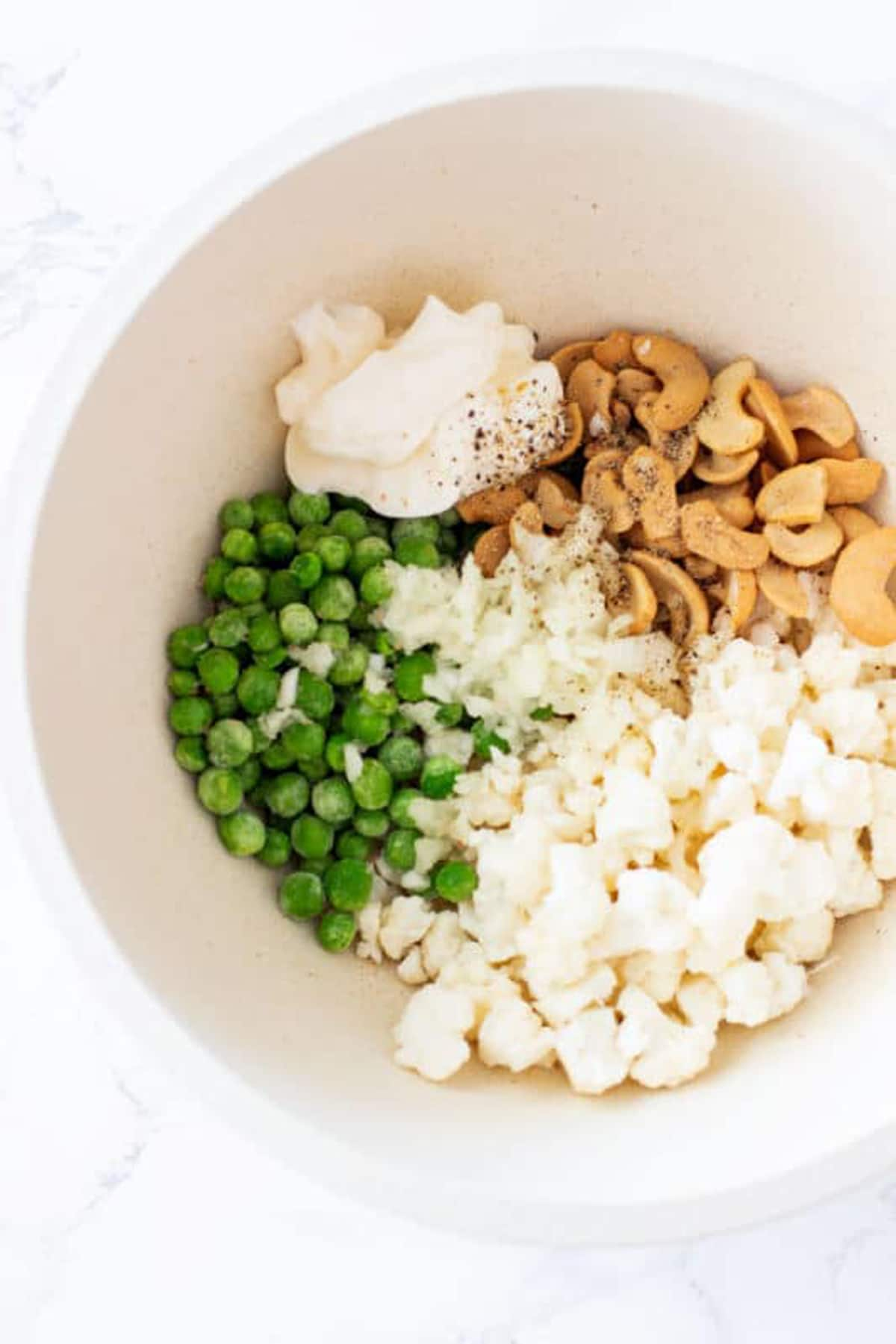 Bowl containing frozen peas, cashew halves, cauliflower, onion and mayonnaise topped with salt and pepper.
