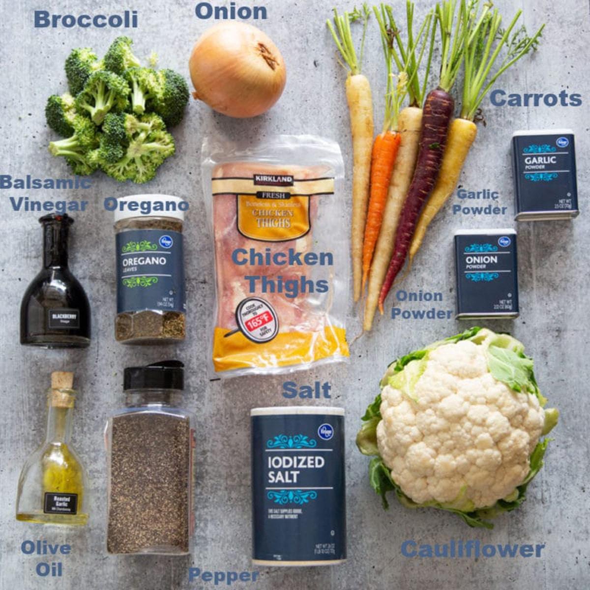 Broccoli, chicken thighs, onion, carrots, cauliflower, olive oil, balsamic vinegar, seasoning on counter.