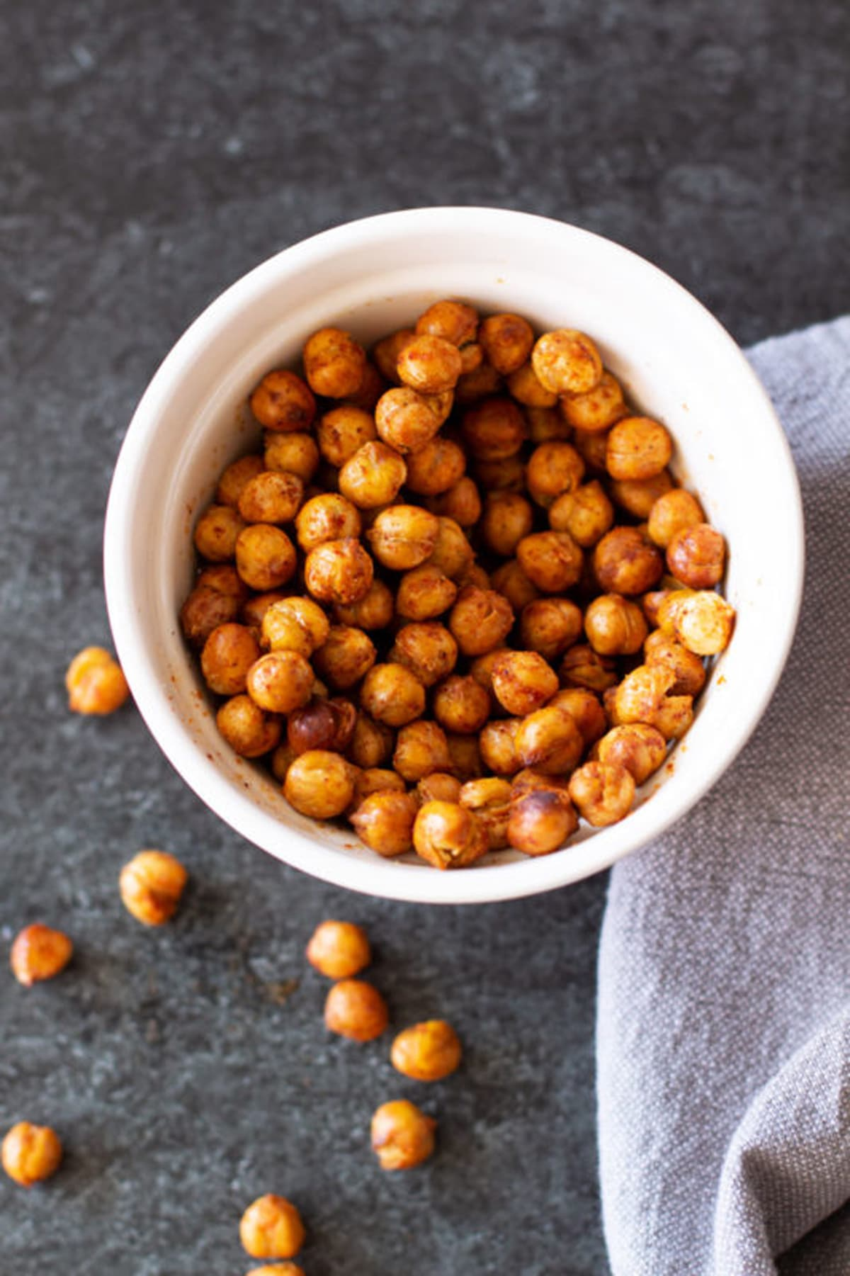 White bowl containing chili lime seasoned chickpeas on a black counter.