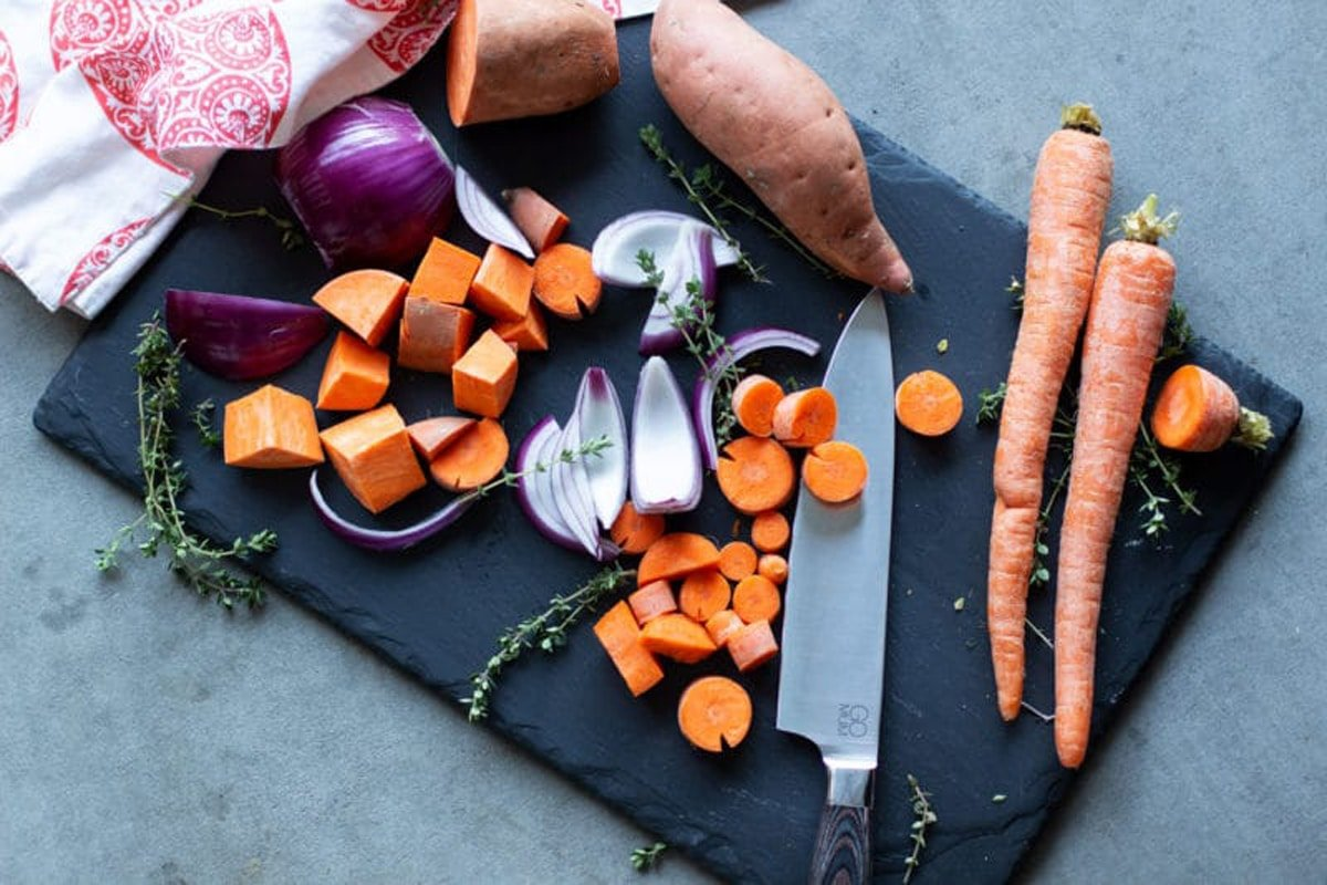 Black cutting board with chopped sweet potatoes, red onion, and carrots.