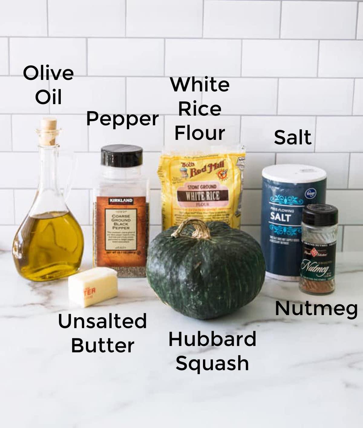 Olive oil, hubbard squash, butter, salt, pepper, nutmeg on counter.