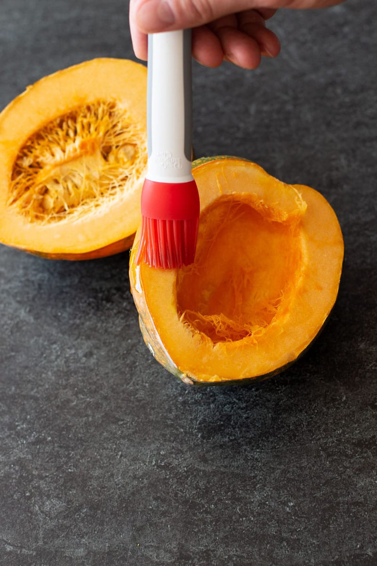 Person basting olive oil on a squash.