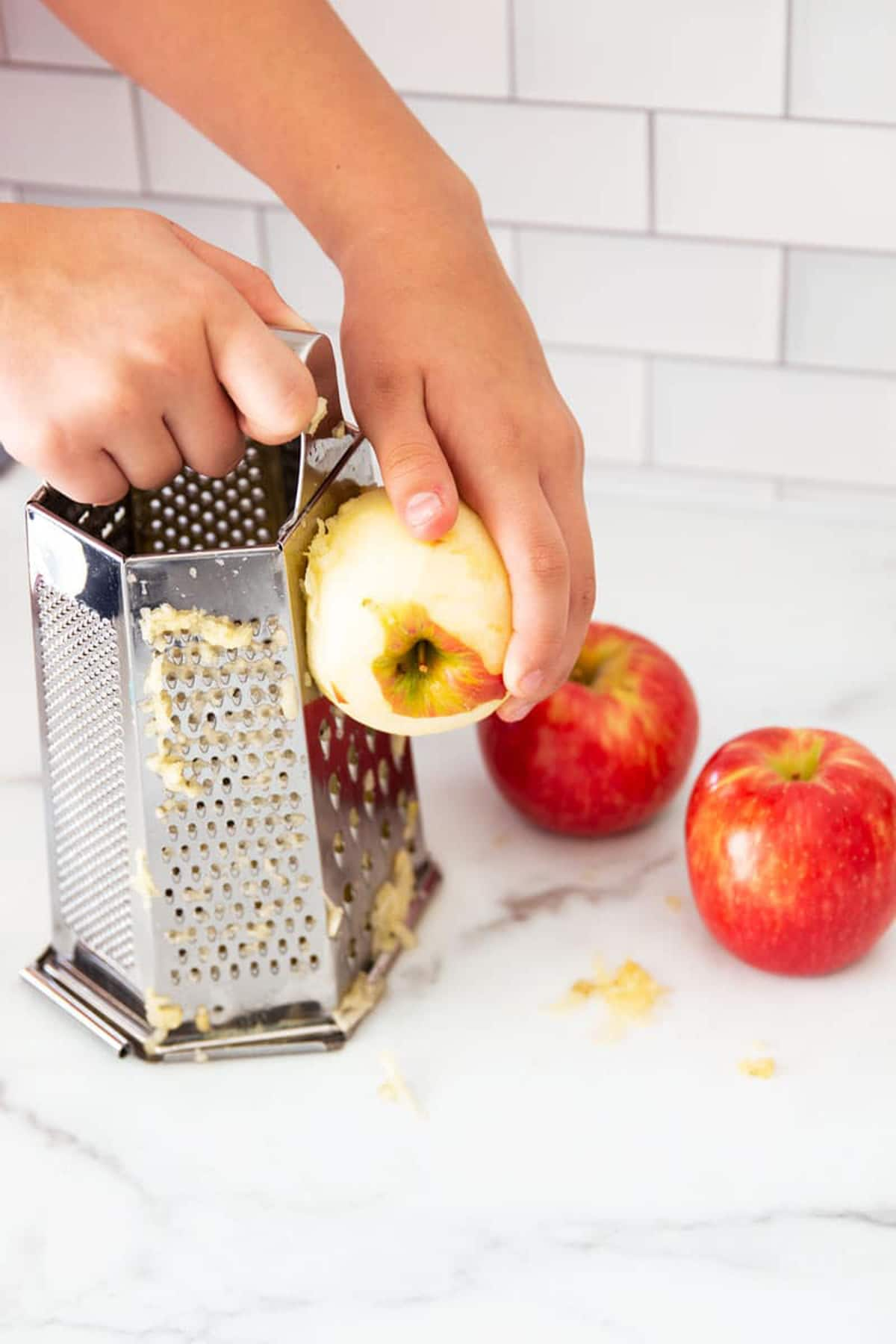 Person grating a peeled apple.