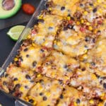 Beef enchilada casserole cut into 12 pieces, avocado, lime, and lettuce on table.