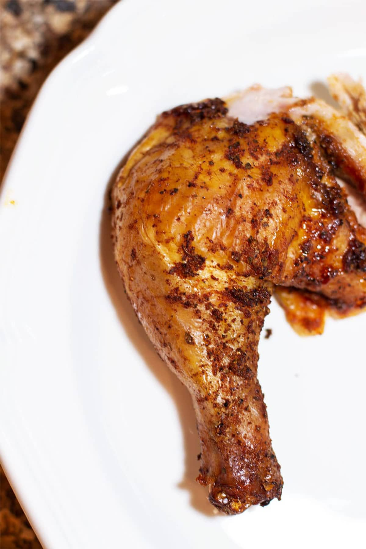 Smoked Applewood chicken leg on a white plate.