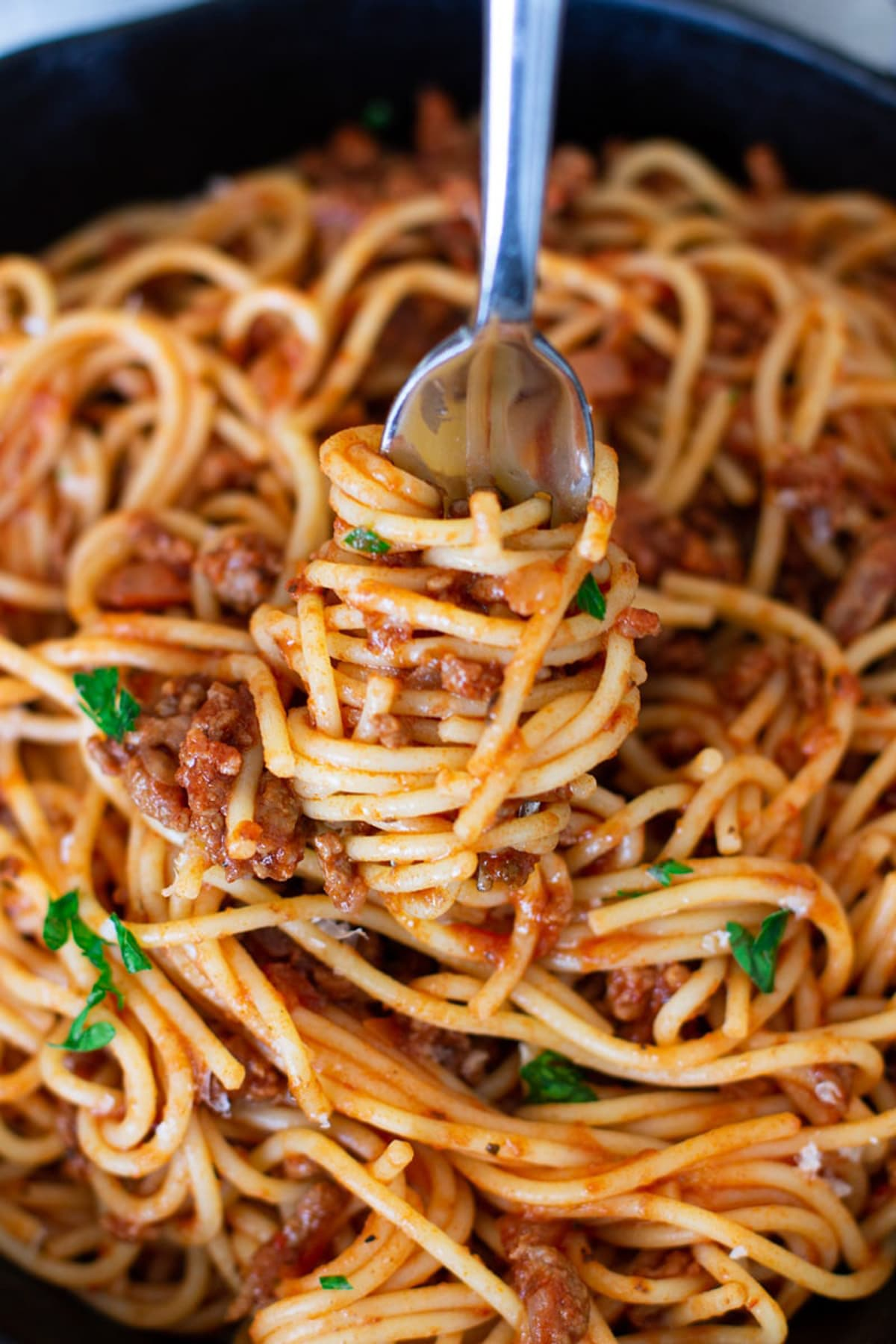 Fork twirled with spaghetti noodles covered in a red marinara sauce.