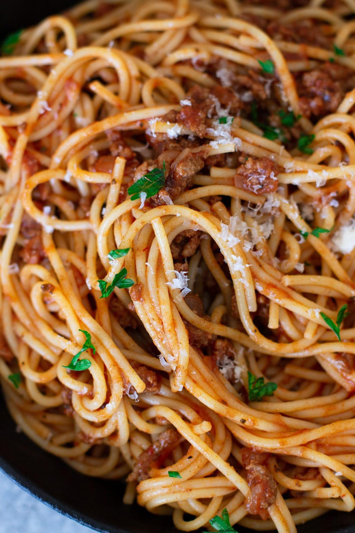 Close up of spaghetti noodles covered in a red sauce topped with parmesan cheese and parsley.