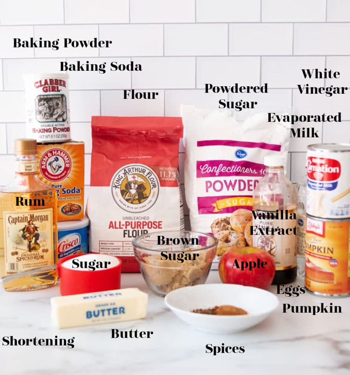 Flour, baking soda and powder, rum, powdered sugar, pumpkin puree, evaporated milk, vanilla extract, butter, eggs, spices on counter.