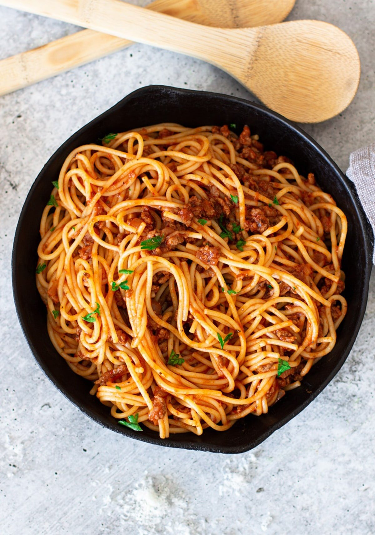 Skillet containing noodles and marinara sauce, spoons on table.