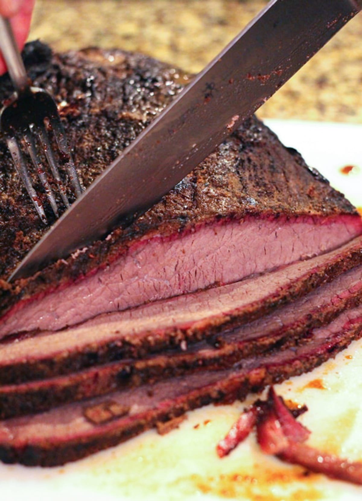 Person slicing a brisket with a knife against the grain.
