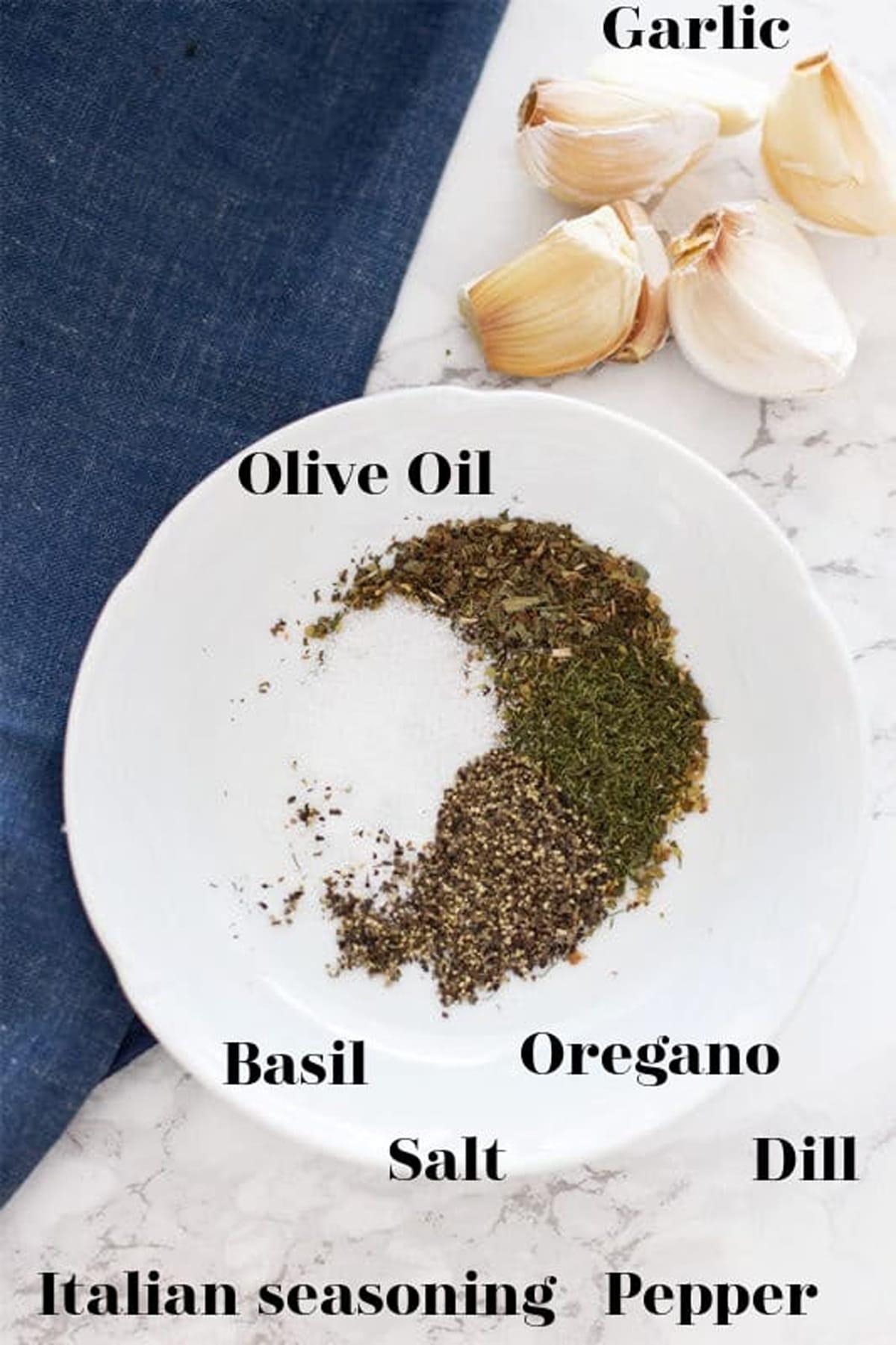 White bowl containing basil, salt, oregano, dill, Italian Seasoning, pepper, olive oil, and garlic cloves.