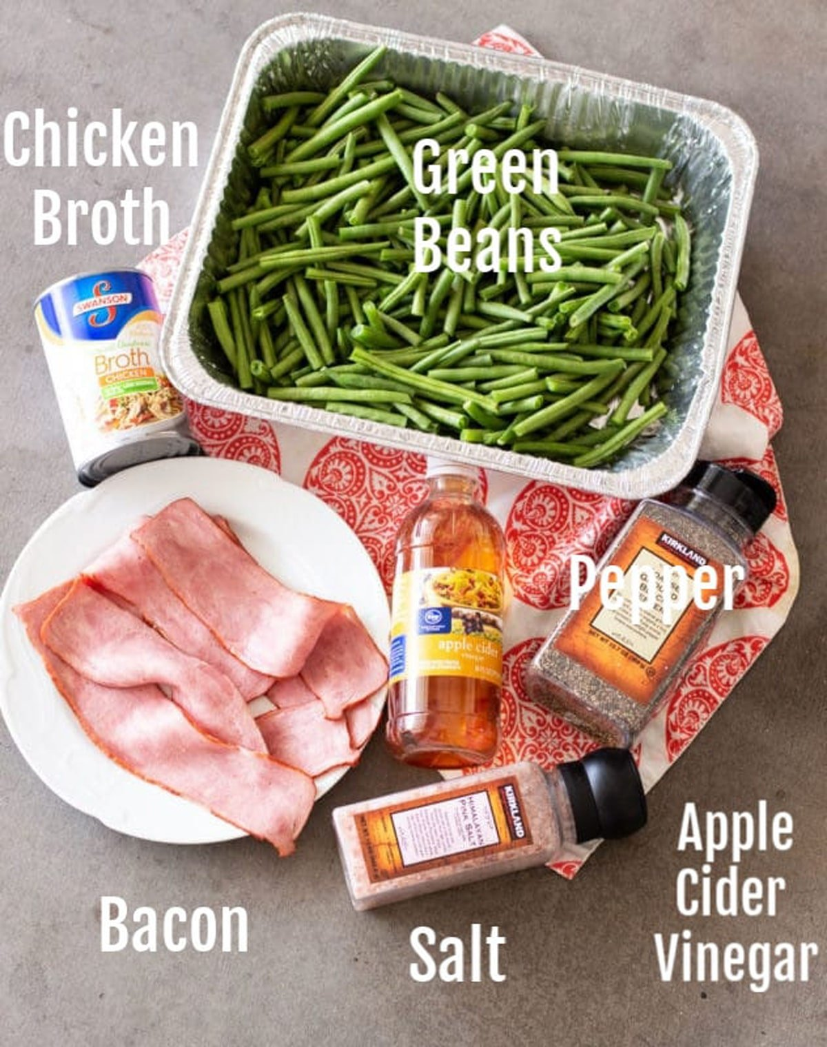 Pan of green beans, chicken broth, bacon, apple cider vinegar, salt and pepper on a table.