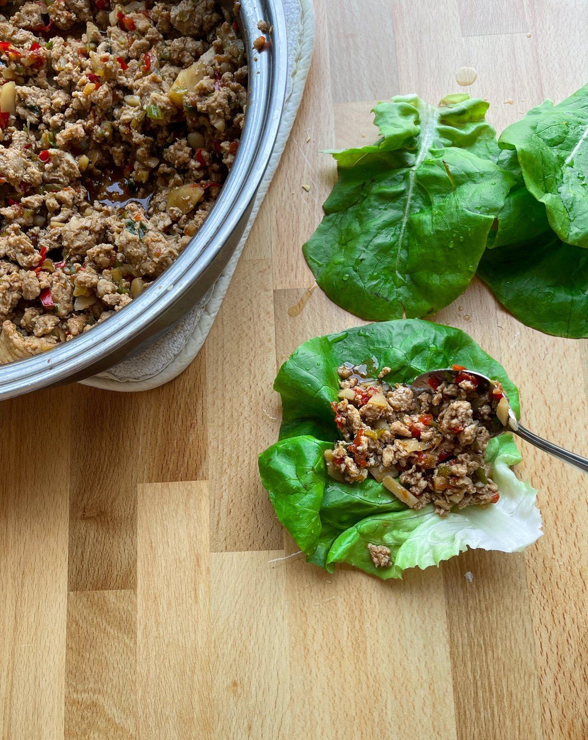 Person scooping Asian lettuce wrap mixture into fresh lettuce leafs.