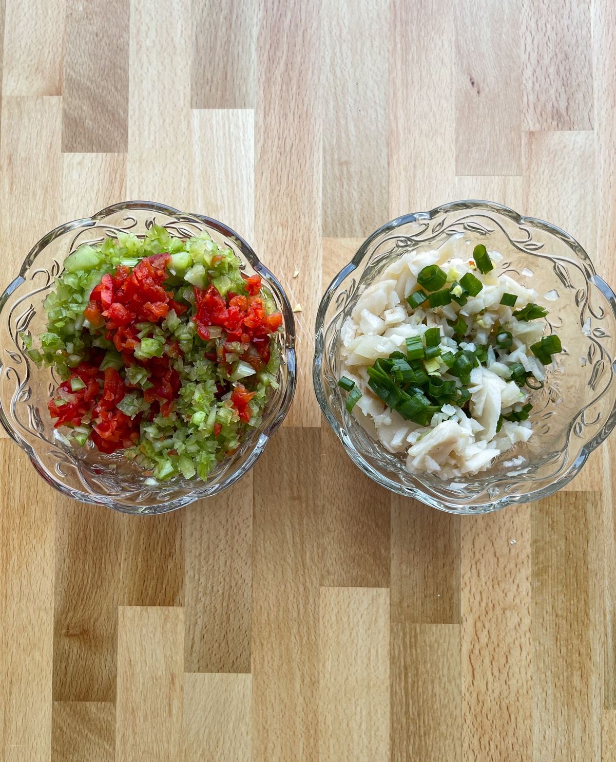 Two glass bowls filled with chopped red pepper, celery, scallions, and water chestnuts.