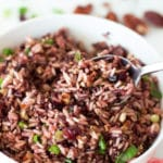 Spoonful of brown and wild rice topped with scallions.