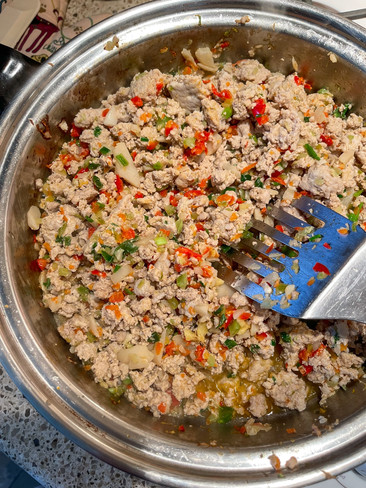 Ground turkey meat in a skillet with sauteed vegetables.