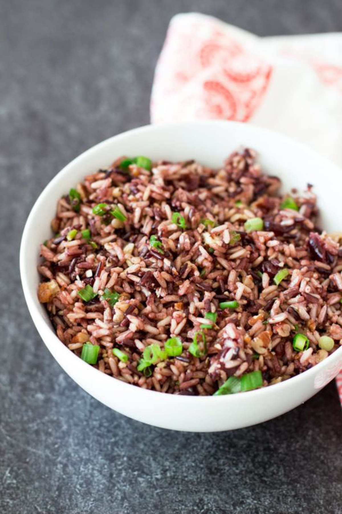 White bowl containing rice topped with scallions.